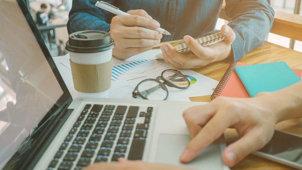 Kuvituskuva. Kaksi ihmistä istuu pöydän ääressä. Toinen kirjoittaa läppärillä ja toisella on kädessä vihko ja kynä. Pöydällä on papereita, silmälasit ja mukillinen take away -kahvia.
