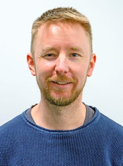 Vaaleahiuksinen mies, jolla on lyhyt parta ja sininen paita päällä.