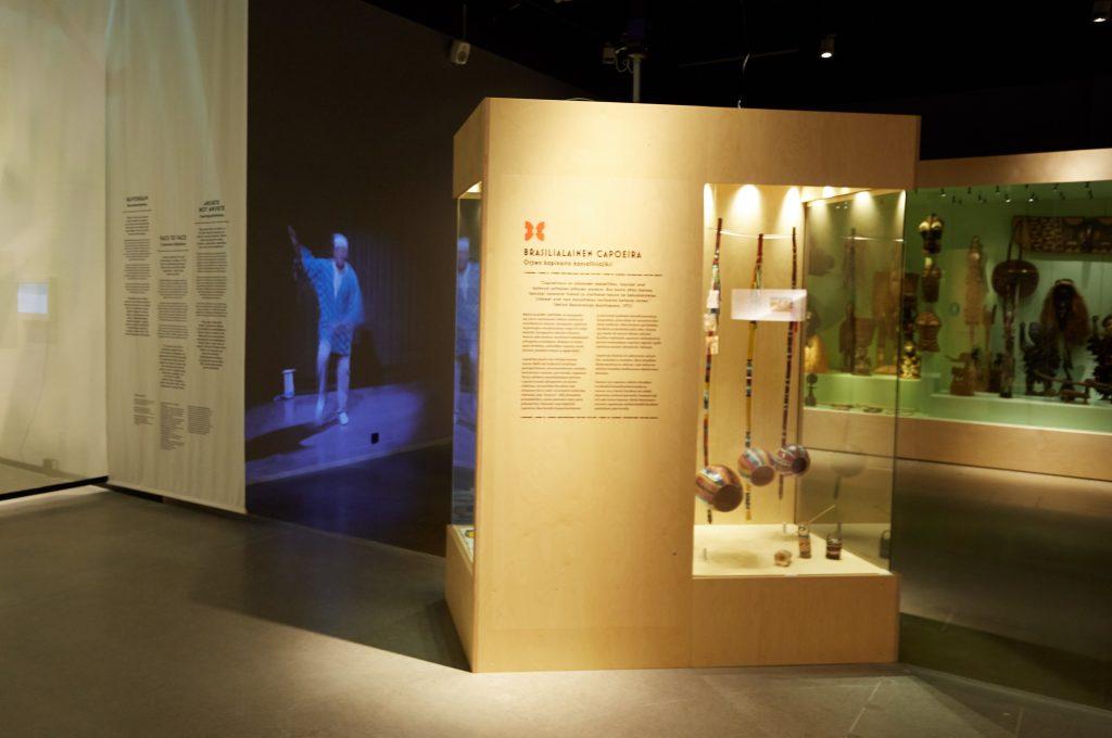 Museon hämärä näyttelytila. Esillä brasilialaisessa capoeirassa käytettäviä välineitä.